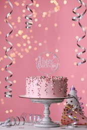 Beautiful birthday cake and decor on white table against blurred festive lights