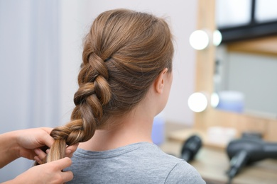 Professional coiffeuse braiding client's hair in salon