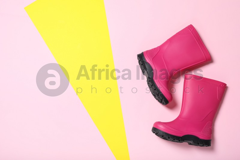 Bright pink rubber boots on color background, top view. Space for text