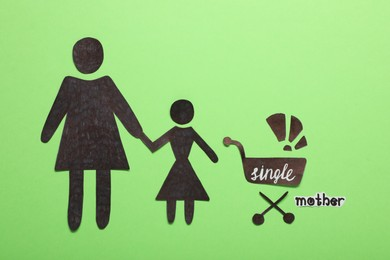 Being single mother concept. Woman with her children made of paper on green background, flat lay