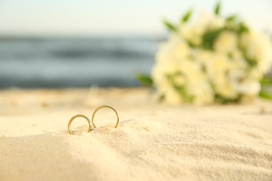 Beautiful gold wedding rings on sandy beach, closeup. Space for text