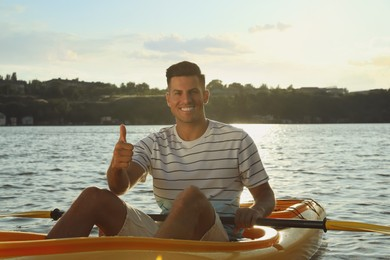 Happy man showing thumb up while kayaking on river. Summer activity