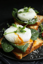 Delicious poached egg sandwiches served on slate board, closeup