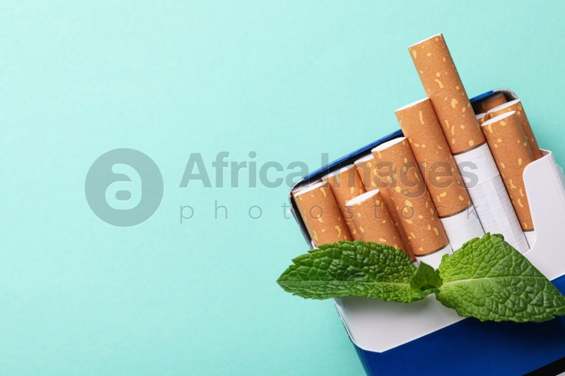 Pack of menthol cigarettes and mint on turquoise background, top view. Space for text