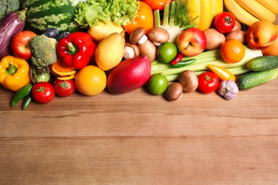 Assortment of fresh organic fruits and vegetables on wooden table, flat lay. Space for text