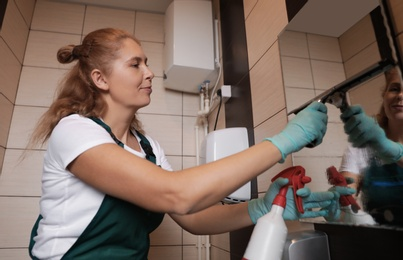 Professional janitor cleaning mirror with supplies in restroom