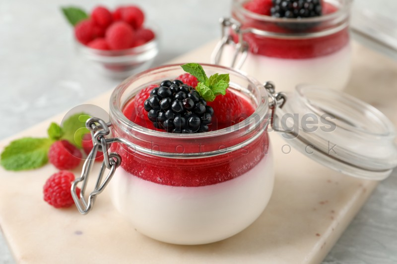 Delicious panna cotta with fruit coulis and fresh berries on light table