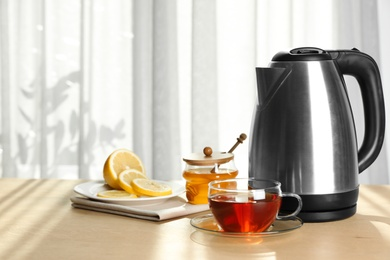 Modern electric kettle and cup of tea on wooden table indoors. Space for text
