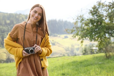 Happy woman with camera on meadow in mountains