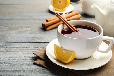 Delicious hot tea with cinnamon and lemon on grey wooden table. Space for text