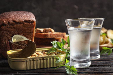 Cold Russian vodka with snacks on black wooden table, closeup