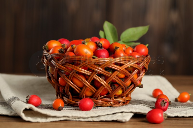 Ripe rose hip berries with green leaves on wooden table