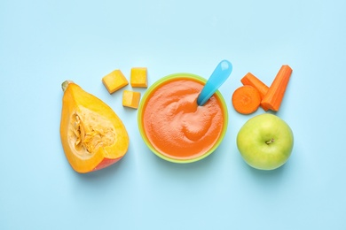 Healthy baby food and ingredients on light blue background, flat lay
