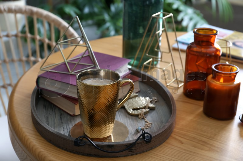 Wooden tray with decorations, books and hot drink on table indoors