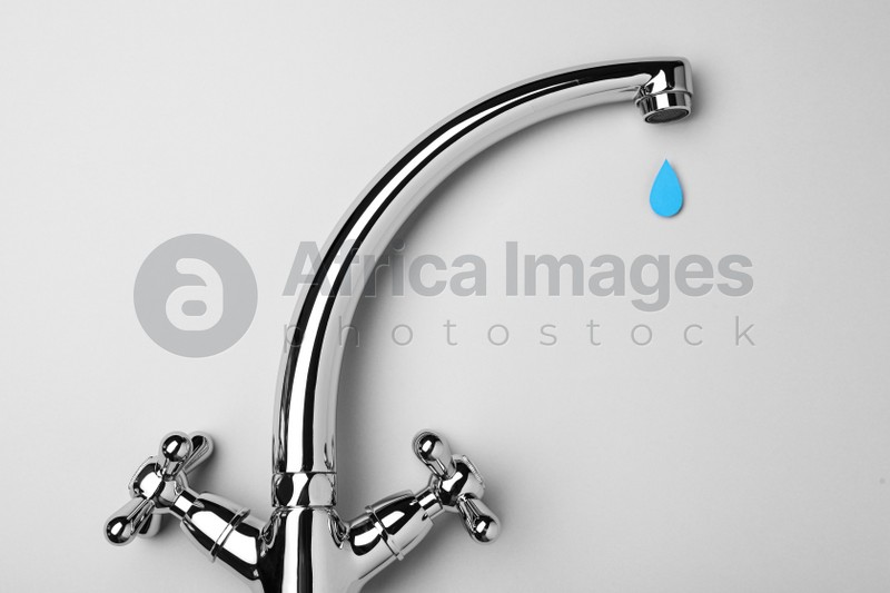 Paper water drop and modern faucet on grey background, flat lay