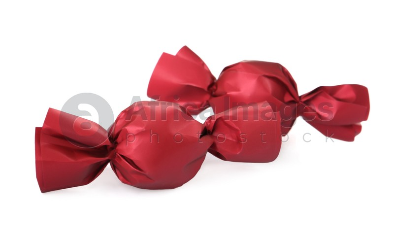 Delicious candies in red wrappers isolated on white