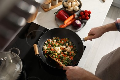 Man stirring mix of fresh vegetables in frying pan, above view