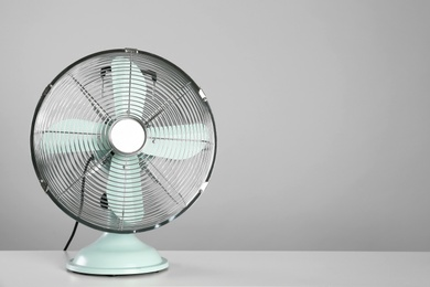 Electric fan on table against light grey background, space for text. Summer heat