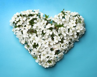 Heart made of beautiful fresh spring flowers on color background, top view