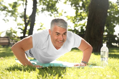 Handsome mature man doing exercise in park. Healthy lifestyle