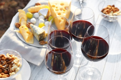 Red wine and snacks served for picnic on white wooden table outdoors