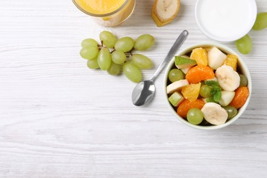 Delicious fresh fruit salad in bowl on white wooden table, flat lay. Space for text