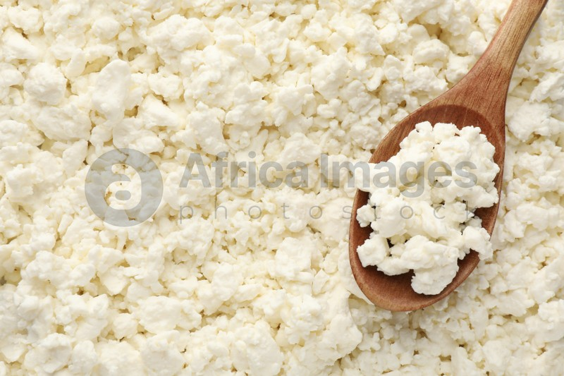 Delicious fresh cottage cheese and spoon as background, top view