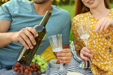 Young couple with wine and glasses having picnic outdoors, closeup