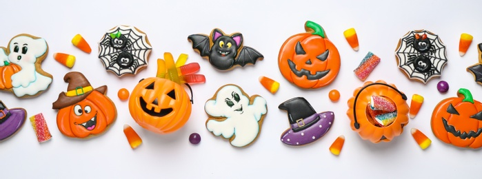 Tasty cookies and sweets for Halloween party on white table, flat lay