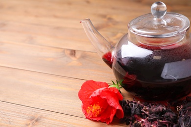 Freshly brewed hibiscus tea on wooden table, closeup. Space for text
