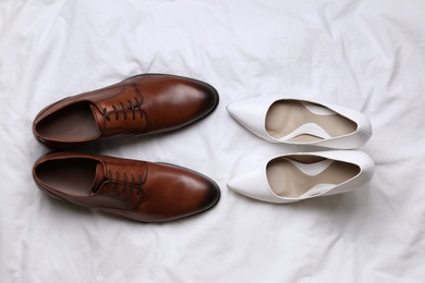 Wedding shoes for bride and groom on white fabric, flat lay