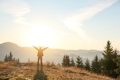 Man enjoying sunrise in mountains, back view. Space for text