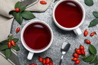 Fresh rose hip tea and berries on grey table, flat lay