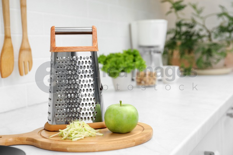 Grater and fresh ripe apple on kitchen counter. Space for text