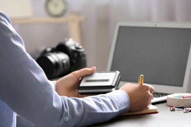 Journalist with voice recorder working at table in office, closeup