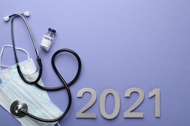 Flat lay composition with coronavirus vaccine on and number 2021 violet background, space for text