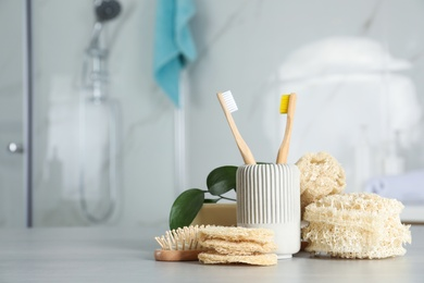 Composition with natural loofah sponges on table in bathroom. Space for text