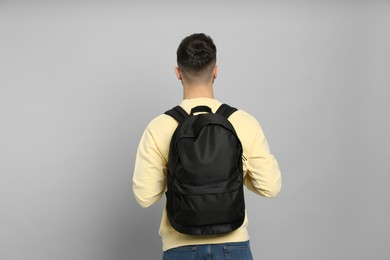 Young man with stylish backpack on light grey background, back view