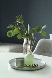 Eucalyptus branches, candle and aromatic reed air freshener on white table indoors. Interior elements