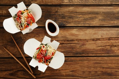 Boxes of vegetarian wok noodles with chopsticks and soy sauce on wooden table, flat lay. Space for text