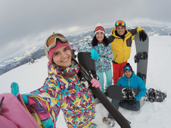Group of friends with equipment taking selfie at ski resort. Winter vacation