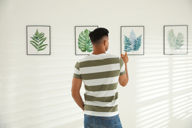 Man at exhibition in art gallery, back view