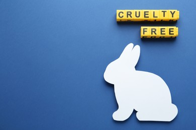 Flat lay of cubes with phrase Cruelty Free and rabbit figure on blue background, space for text. Stop animal tests