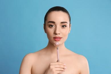 Woman using natural pink quartz face roller on light blue background