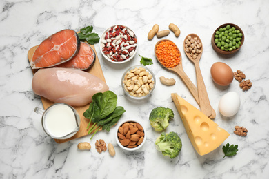 Products rich in protein on white marble table, flat lay