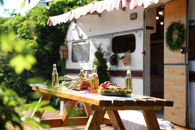 Wooden table with food and bottles of beer near motorhome on sunny day. Camping season