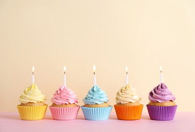 Delicious birthday cupcakes with burning candles on pink table against beige background