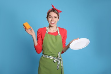 Young housewife with plate and sponge on light blue background