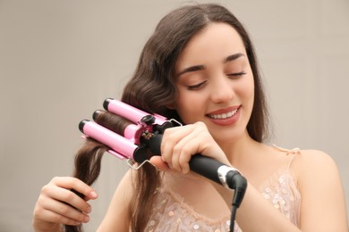 Young woman using modern curling iron indoors