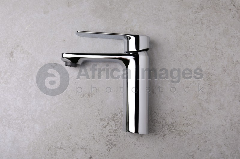 Single handle water tap on grey table, top view